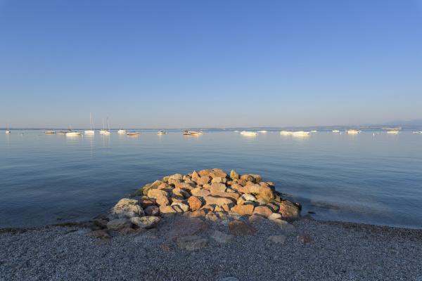 solbeskinnede klipper stablet pa stranden ved