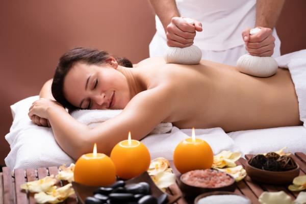 terapeut giver massage med urte komprimere