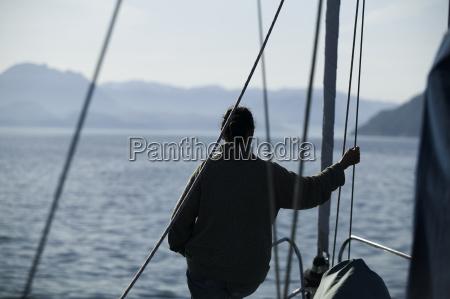 person pa sejl yacht baggrundslys fjord
