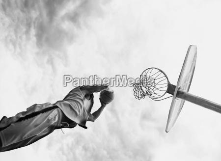 man spiller basketball