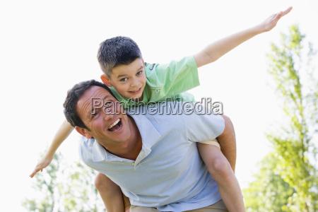 man giver ung dreng piggyback tur