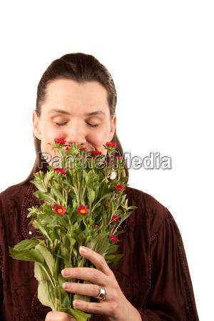 smuk kvinde lugtende blomster