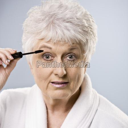 AEldre kvinde saette pa makeup
