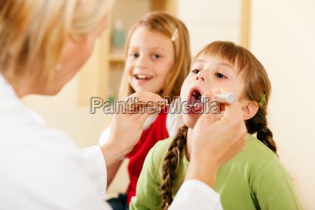 laege undersoger hals af et barn
