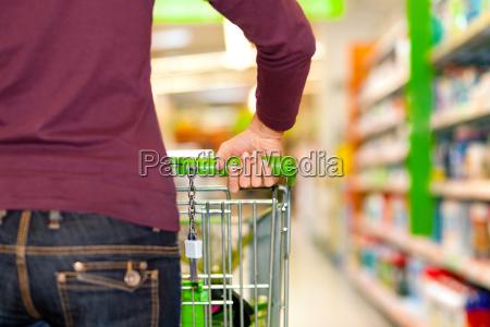 kvinde i supermarked med indkobskurv