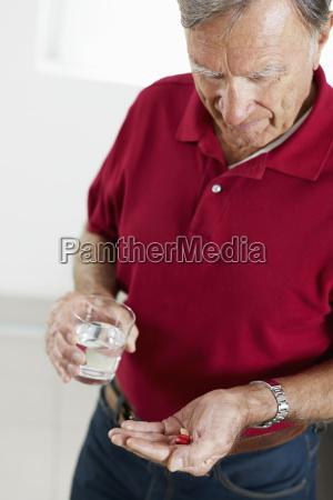 senior mand tager medicin