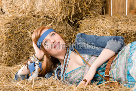 young hippie woman lying on hay