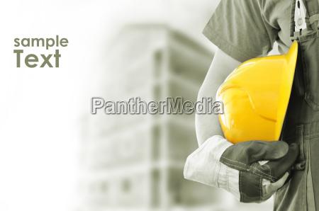 worker med sloret byggeri i baggrunden
