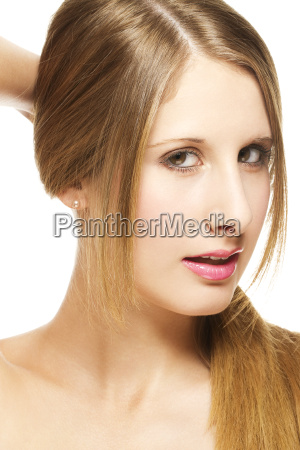 young blond woman holding hair to
