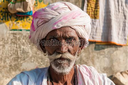 en gammel siddende indisk mand med