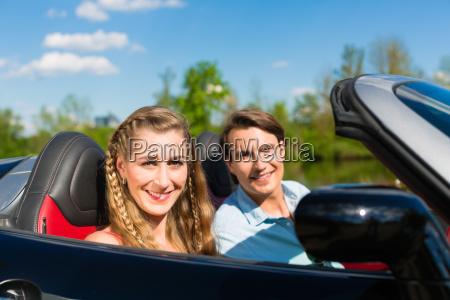 ungt par med cabriolet om sommeren