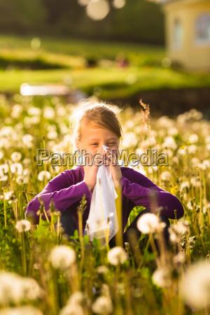 pigen sidder pa eng med maelkebotter