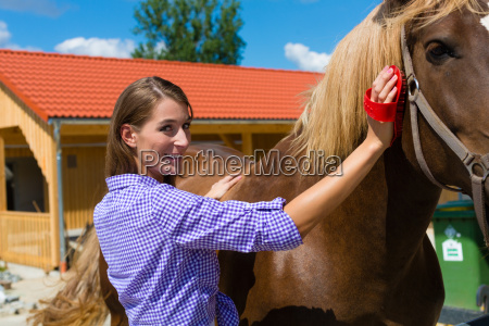 young woman in stable with horse