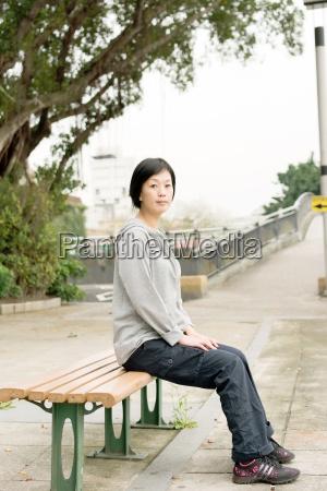 kvinde sidder pa baenken
