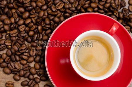 rod kop espresso og brune kaffebonner