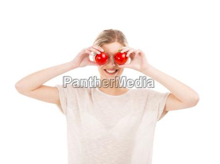 behagelig kvinde med tomater foran ansigtet