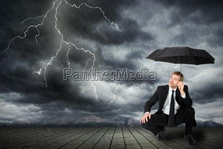mand i jakkesaet og paraply soger
