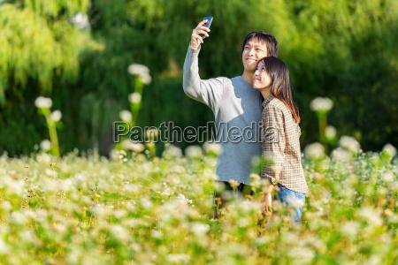 asiatiske par tage foto via mobiltelefon