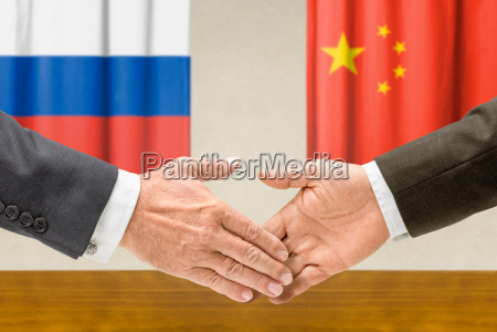 vertreter russlands und chinas reichen sich