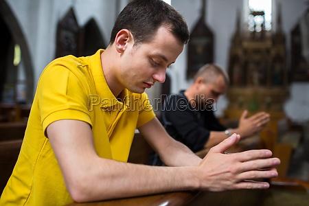 smuk ung mand beder i en