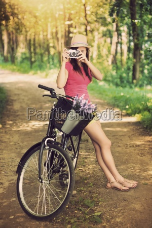 young woman on bike photographing nature
