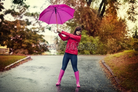 young woman holding pink umbrella in