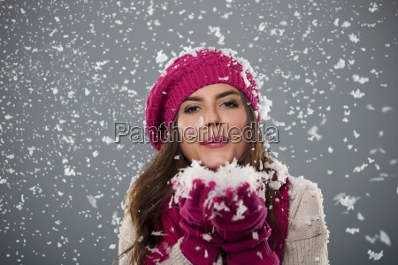 beautiful young woman blowing snow