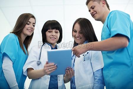 medical team checking results on digital