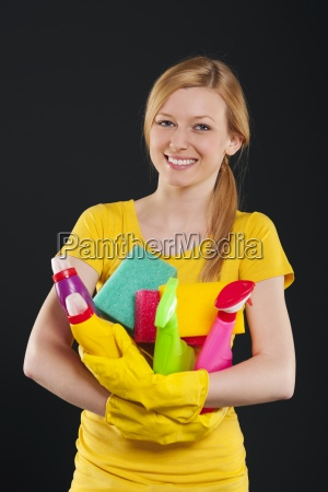happy blonde woman holding cleaning equipment