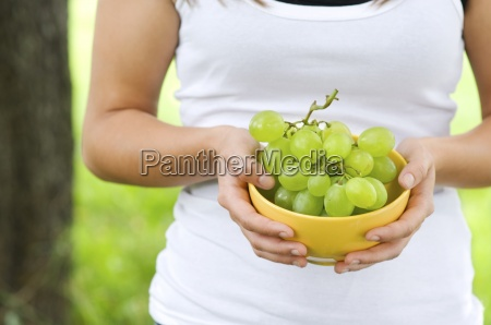 young woman holding bowl with grapes