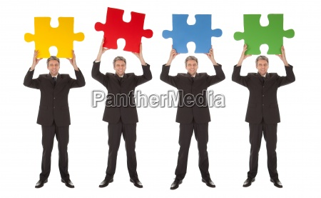 group of business people holding jigsaw