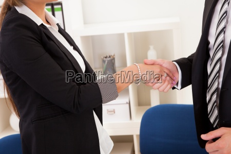 business mand og kvinde ryster haender