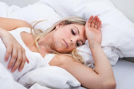 upset kvinde liggende pa sengen