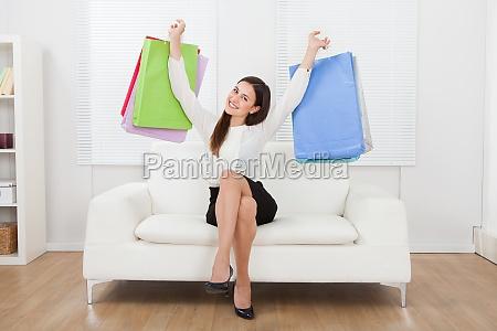 begejstret forretningskvinde holde indkobsposer pa sofaen