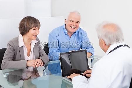 lykkelige par diskutere med mandlig laege