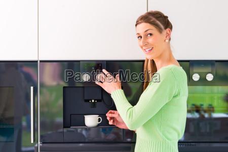 kvinde drikker kop kaffe i kokkenet