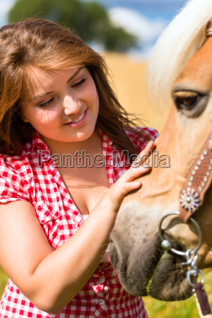woman is riding on horse in