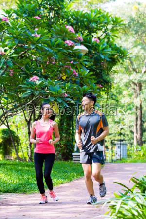 asiatisk kinesisk mand og kvinde jogging