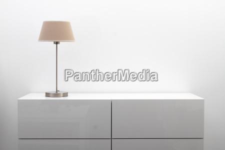 hvid kommode med bordlampe i lyse