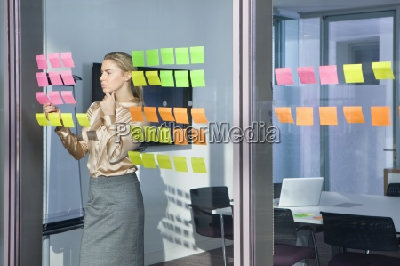 pensive forretningskvinde kigger pa klaebende noter