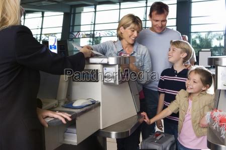 familie checker ind i lufthavnen check