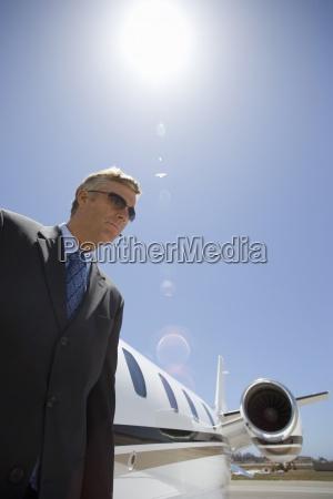 forretningsmand med fly pa landingsbanen lav