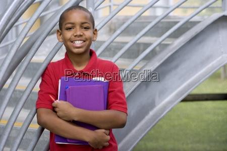 boy 10 12 with school books