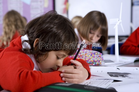 concentrating school boy covering work in