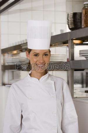 kvindelige kok staende i kommercielle kokken