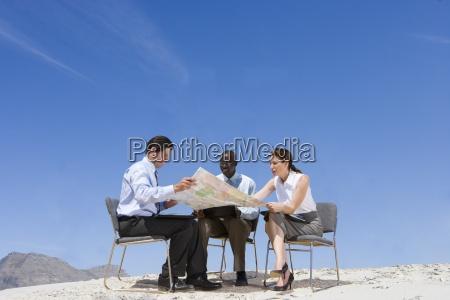 forretningsfolk kigger pa kort i fjerntliggende