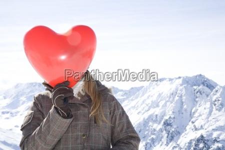junge frau mit roten herzfoermigen luftballon