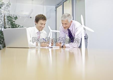 to forretningsmaend diskuterer vindmolle teknologi