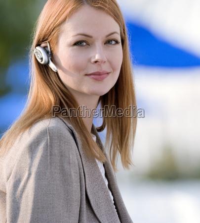 forretningskvinde ifort mobiltelefon handfri enhed smilende