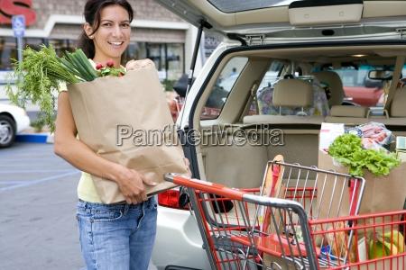 kvinde lastning bil med indkobsposer fra